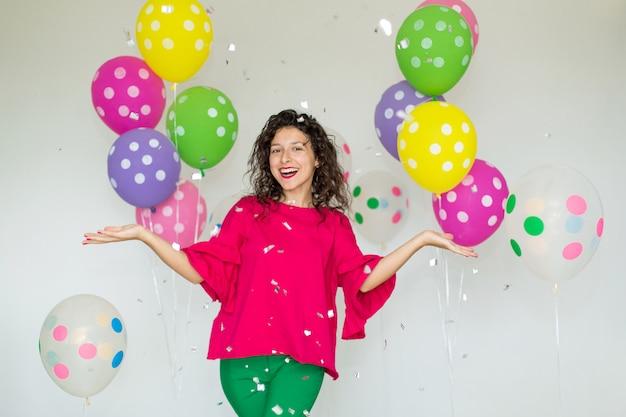Piękna śliczna rozochocona dziewczyna z kolorowymi balonami śmia się i rzuca confetti