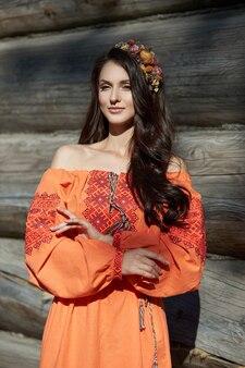 Piękna słowianka w pomarańczowej sukience etnicznej i wieńcu z kwiatów na głowie