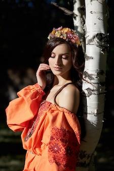 Piękna słowiańska kobieta w pomarańczowej sukience etnicznej i wieńcem z kwiatów na głowie. piękny naturalny makijaż. portret rosyjskiej dziewczyny
