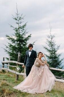 Piękna ślub para całuje i obejmuje blisko brzeg halnej rzeki z kamieniami