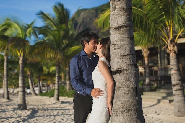 Piękna ślub para na plażowym pobliskim drzewku palmowym