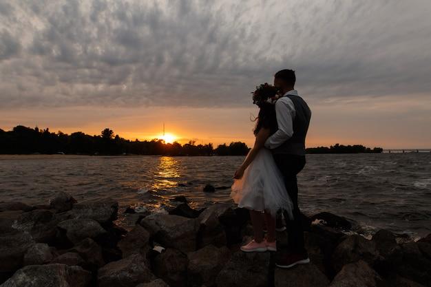 Piękna ślub para na skalistej plaży. stylowi nowożeńcy w tenisówkach trzymający się za ręce i przytulający się na zewnątrz o zachodzie słońca. narzeczeni stojący na brzegu morza. dzień ślubu na łonie natury. romantyczna data