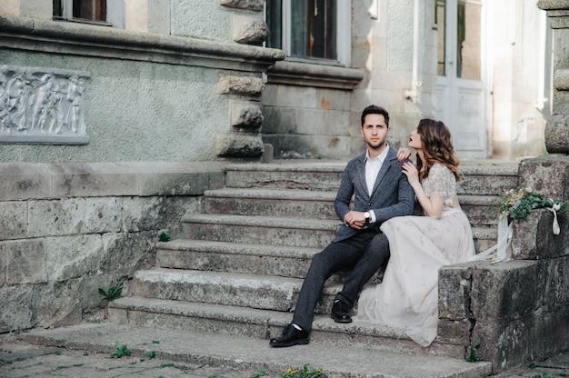 Piękna ślub para na zewnątrz zamku na schodach