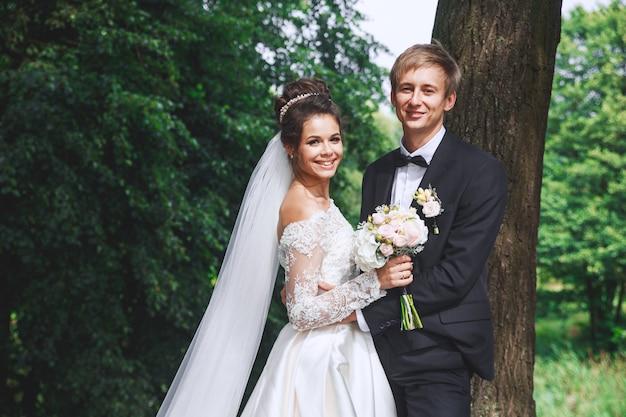 Piękna ślub para w parku. narzeczeni przytulają się na zewnątrz