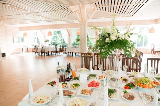 Piękna ślubna dekoracja kwiatowa na stole z jedzeniem cateringowym w jasnej sali restauracyjnej z białymi obrusami