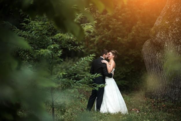Piękna ślubna para w ramionach siebie w parku