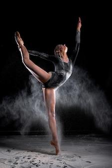 Piękna smukła tancerka baletowa kobieta nosi body, pozowanie, taniec wśród chmury latającej mąki na tle czarnego studia, sprawiają, że wydajność. projekt artystyczny, komercyjny, monochromatyczny.
