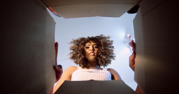 Piękna smutna brunetka z kręconymi włosami otwierająca pudełko z zamówieniem otrzymanym na poczcie lub firmie kurierskiej. brazylijska młoda kobieta odbiera rozkaz.