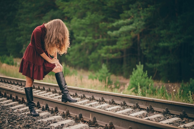 Piękna smutna dziewczyna ukrywa twarz za włosami. nastrojowa dama w bordowej sukience w lesie na kolei.