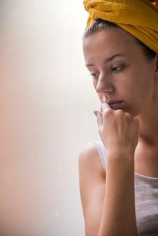 Piękna, smutna, samotna dziewczyna siedząca przy oknie. samotna dziewczyna smutku smutna przy oknie