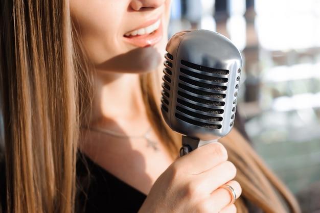 Piękna śpiewająca dziewczyna. piękna kobieta z mikrofonem.