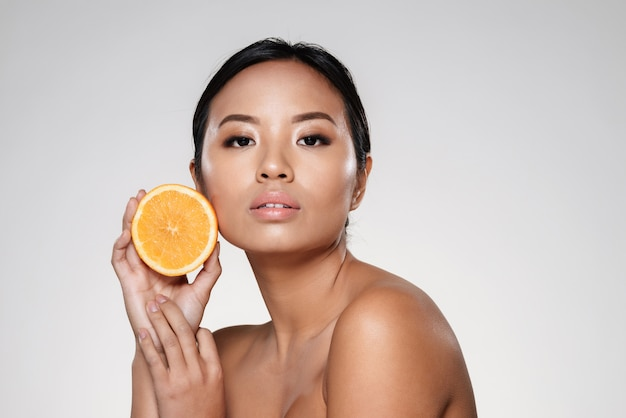 Piękna spokojna kobieta pokazuje pomarańczowego plasterek i przyglądającą kamerę