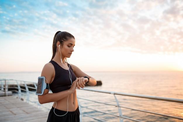 Piękna sportive dziewczyna patrzeje zegarek podczas wschodu słońca nad nadmorski.