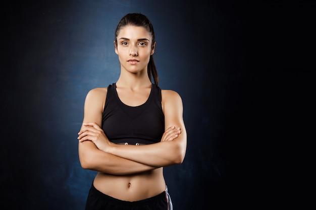 Piękna sportive dziewczyna pozuje z krzyżować rękami nad zmrok ścianą.