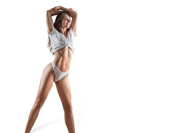Piękna sportive kobieta pozuje w studio na białym tle. fitness, kulturystyka, koncepcja aerobiku. różne środki przekazu