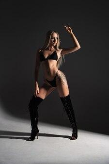 Piękna sportive kobieta pozuje w studio na czarno-białym tle fitness kulturystyka