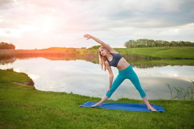 Piękna sportowa blondynki dziewczyna ćwiczy joga na jeziorze przy zmierzchem, zakończenie, wspiera zdrowego styl życia