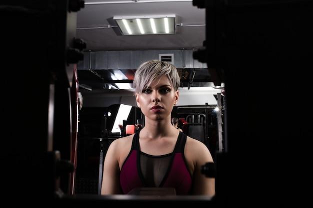 Piękna sportowa dziewczyna jest zaangażowana w symulator na siłowni