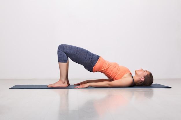 Piękna, sportowa dziewczyna jogin ćwiczy bandany jogi asana setu