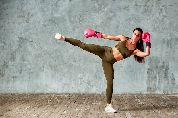 Piękna sportowa dziewczyna pozuje w różowych bokserskich rękawiczkach na szarej przestrzeni. skopiuj miejsce sport koncepcyjny, walka, osiągnięcie celu.