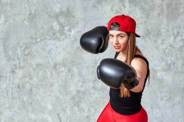 Piękna sportowa dziewczyna pozuje w różowych bokserskich rękawiczkach na szarej ścianie. kopiowanie miejsca, zbliżenie. sport koncepcyjny, walka, osiągnięcie celu.