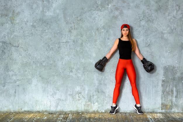 Piękna sportowa dziewczyna pozuje w różowych bokserskich rękawiczkach na szarym tle. skopiuj miejsce sport koncepcyjny, walka, osiągnięcie celu.