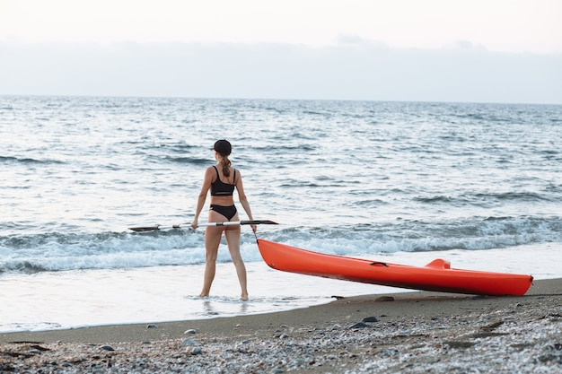 Piękna sportowa dziewczyna w czarnym stroju kąpielowym idzie z pomarańczowym kajakiem, aby popływać w morzu o zachodzie słońca