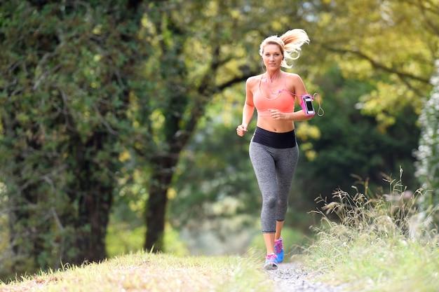 Piękna sportowa kobieta biega w lesie
