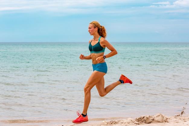 Piękna sportowa kobieta biegnie wzdłuż pięknej, piaszczystej plaży, zdrowego stylu życia, ciesząc się aktywnymi wakacjami w pobliżu morza