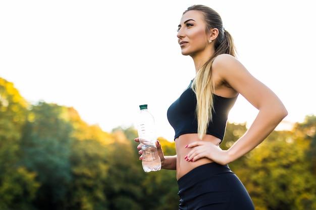 Piękna sportowa kobieta w topie i trampkach na porannym biegu pije wodę z butelki