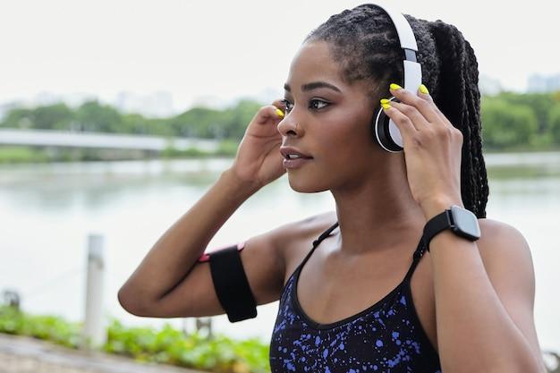 Piękna, sportowa, młoda kobieta rasy mieszanej, zakładająca headphnes przed joggingiem wzdłuż brzegu rzeki rano