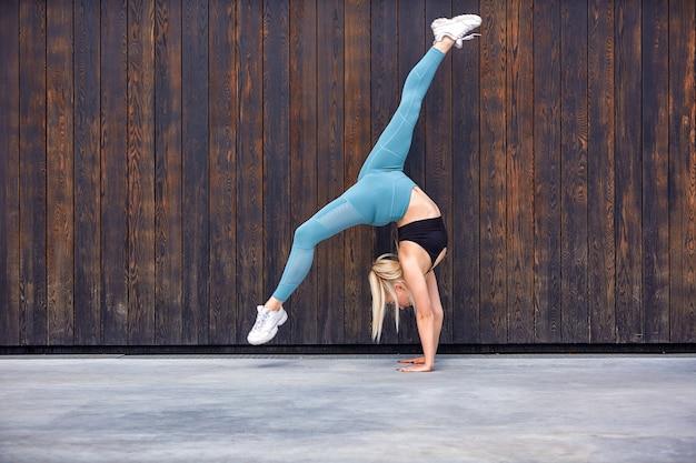 Piękna sportowa młodej kobiety gimnastyczka w sportswear, pracująca out