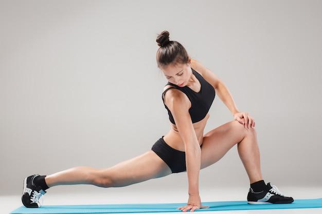 Piękna sporty dziewczyny pozycja w akrobat pozie lub joga asanie