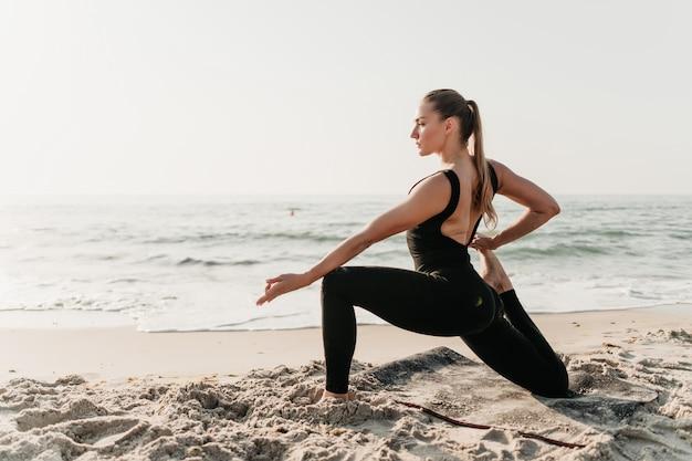 Piękna sporty kobieta robi joga asana na plażowym pobliskim oceanie