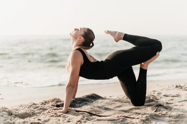 Piękna sporty kobieta robi joga ćwiczeniu na plażowym pobliskim oceanie