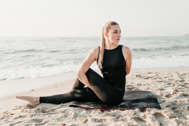 Piękna sporty kobieta robi joga na plażowym pobliskim oceanie