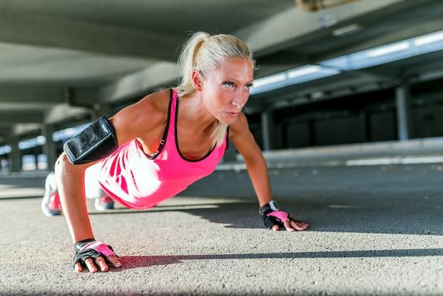Piękna sporty młoda kobieta podnosi outdoors robić pcha.