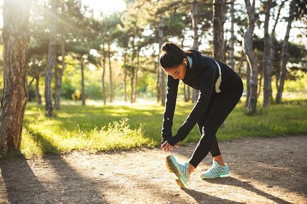 Piękna Sprawna Sportsmenka Robi ćwiczenia Rozgrzewające Przed Joggingiem W Parku, Słuchając Muzyki Przez Słuchawki Premium Zdjęcia