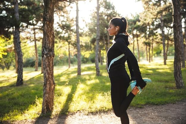 Piękna sprawna sportsmenka robi ćwiczenia rozgrzewające przed joggingiem w parku, słuchając muzyki przez słuchawki