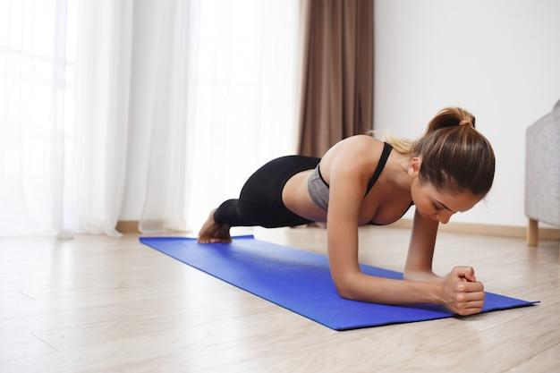 Piękna sprawności fizycznej dziewczyna robi ćwiczeniom sportowym na podłoga