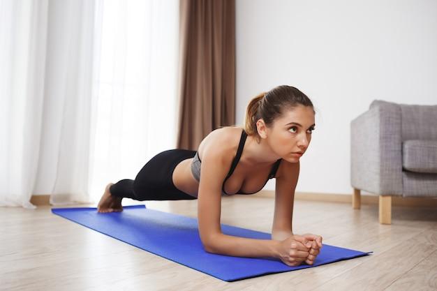 Piękna sprawności fizycznej dziewczyna robi desce ćwiczy na podłoga