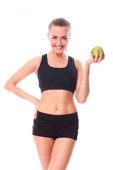 Piękna sprawności fizycznej dziewczyna z zielonym jabłkiem w ręce