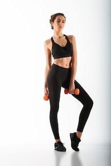 Piękna sprawności fizycznej kobieta pozuje z dumbbells