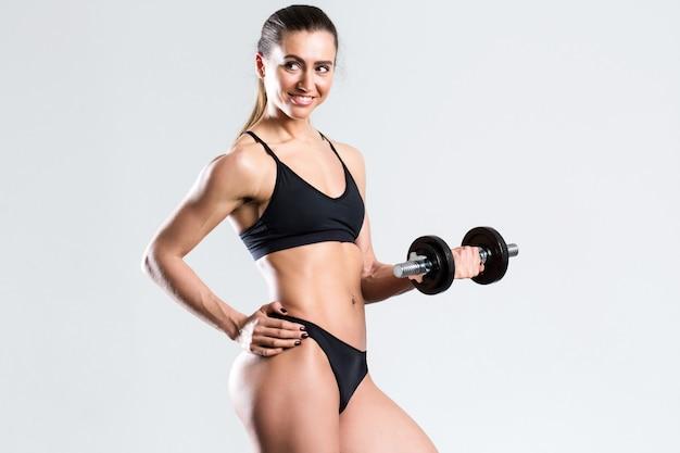 Piękna sprawności fizycznej kobieta pozuje z dumbbells.