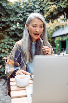 Piękna starsza azjatycka kobieta je świeżą truskawkę przed laptopem przy stole na zewnątrz