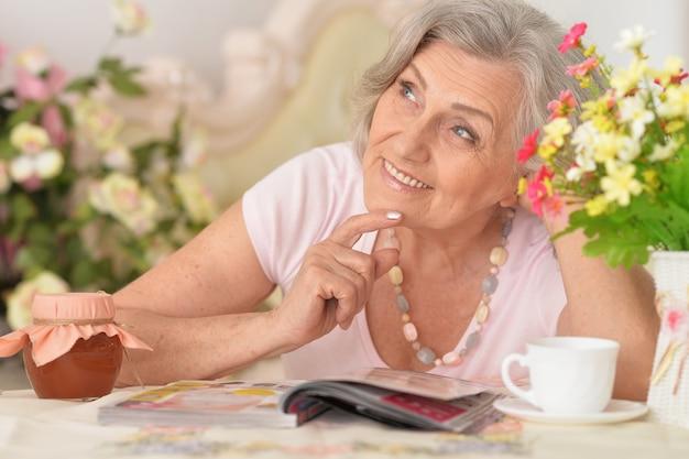 Piękna starsza kobieta czyta magazyn z kwiatami na tle