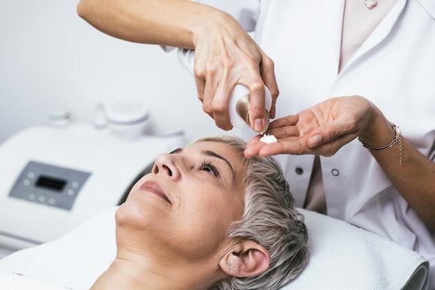 Piękna starsza kobieta o peeling chemiczny zabieg kosmetyczny. ekspert kosmetyczki nakłada na twarz kobiety roztwór chemiczny.