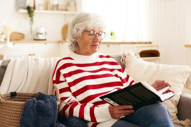 Piękna starsza kobieta o siwych włosach, ciesząc się emeryturą, siedząc na kanapie w salonie, czytając ciekawą powieść. starsze kobiety rasy kaukaskiej w okrągłych okularach relaks w domu z książką