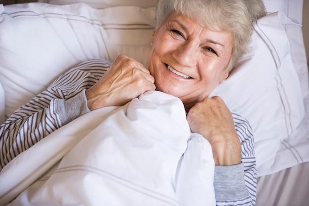 Piękna starsza kobieta odpoczywa w łóżku