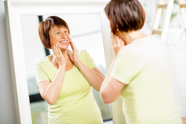 Piękna starsza kobieta patrząca na swoją twarz z uśmiechem w lustrze